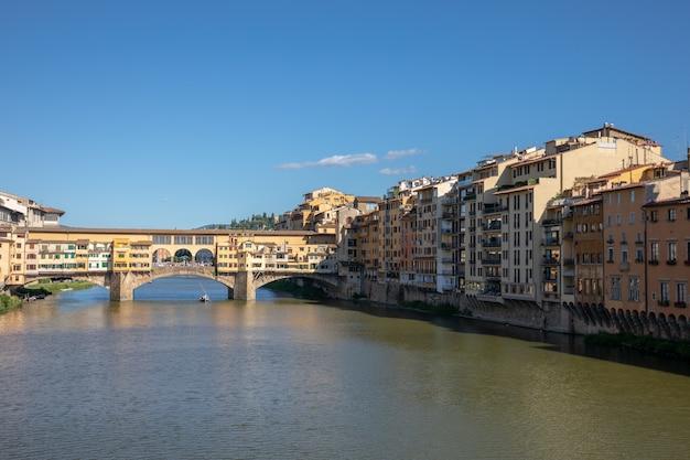 이탈리아 피렌체 - 2018년 6월 26일: 베키오 다리(ponte vecchio)의 탁 트인 전망은 피렌체의 아르노 강(arno river) 위에 있는 중세 석조 폐쇄형 스팬드럴 아치 다리입니다. 여름날과 푸른 하늘