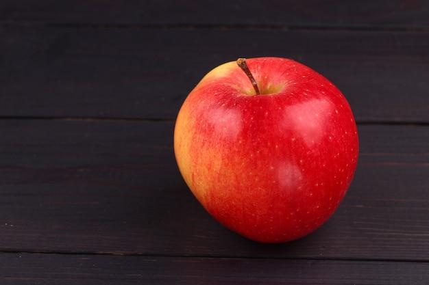 暗い表面にフローリンの赤いリンゴ