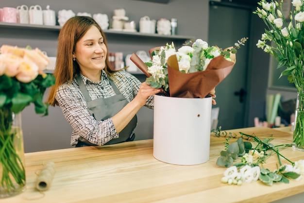 Флорист принимает оплату от покупательницы женского пола