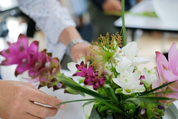 Флорист оформляет букет цветов в вазе.