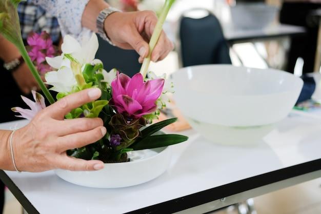 Florist arranging flower bouquet in vase.