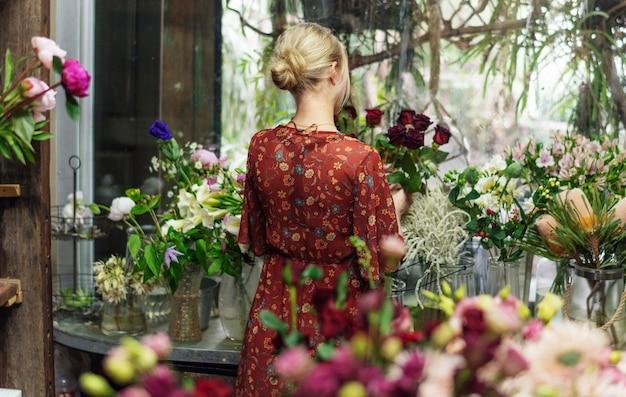 Флорист расставляет розы в своем магазине