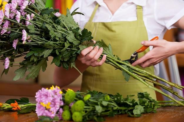 Флорист за работой. обрезанное изображение женского флориста в фартуке срезания цветов