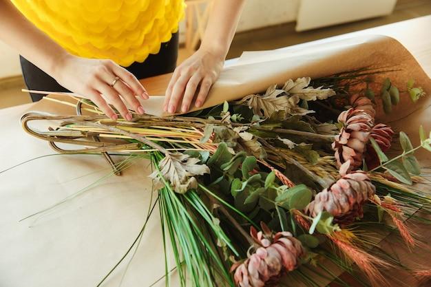 직장에서 플로리스트가 꽃다발 만드는 방법을 보여줍니다.
