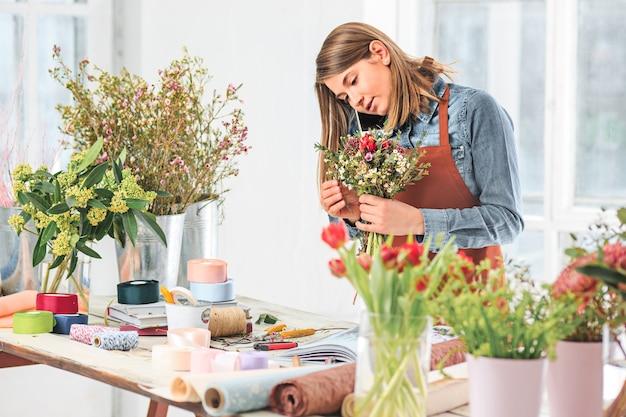 직장에서 꽃집: 다른 꽃의 패션 현대 꽃다발을 만드는 여자의 여성 손