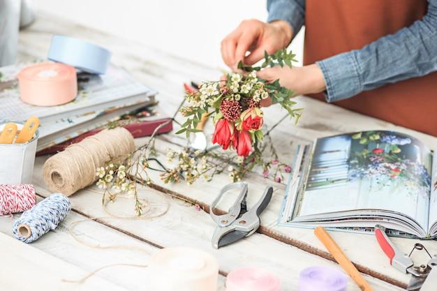 Флорист за работой: женские руки женщины делают модный современный букет из разных цветов