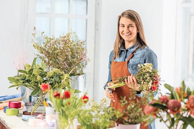 Флорист за работой: молодая девушка делает модный современный букет из разных цветов