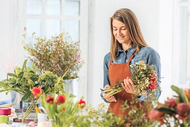 직장에서 꽃집: 다른 꽃의 패션 현대 꽃다발을 만드는 어린 소녀 프리미엄 사진