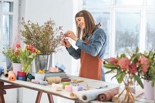 직장에서 꽃집: 다른 꽃의 패션 현대 꽃다발을 만드는 어린 소녀