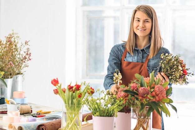 仕事で花屋:さまざまな花のファッションモダンな花束を作る若い女の子