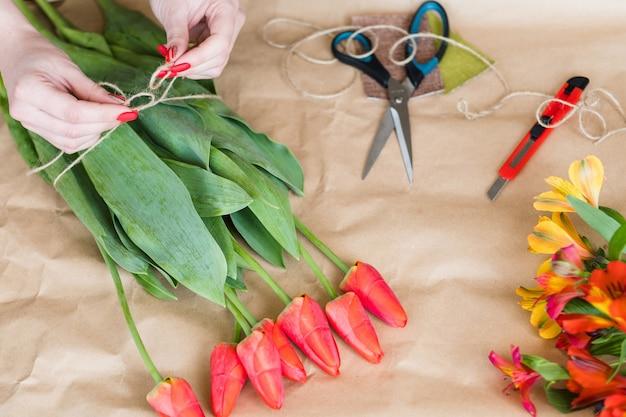 仕事で花屋。チューリップの花束を作る女性の手