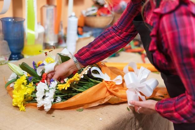 仕事で花屋。花の美しい花束を作る女性の手。