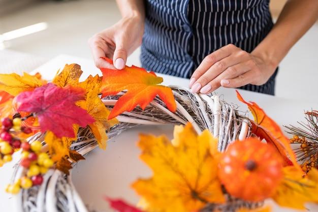 Флорист за работой: женщина делает осенний венок у дверей из желтых листьев