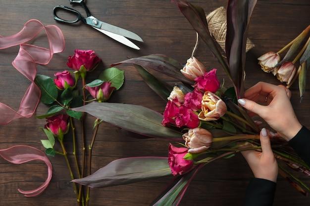 仕事で花屋:木製の背景にさまざまな花のファッションモダンな花束を作る女性。マスタークラス。結婚式、母の、女性の日の花嫁への贈り物。ロマンチックな春のファッション。情熱のバラ。