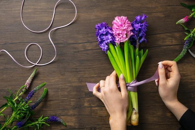 木製の背景にさまざまな花のファッションモダンな花束を作る職場の女性の花屋
