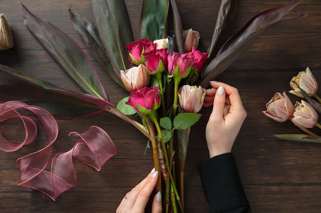 木製の表面にさまざまな花のファッションモダンな花束を作る職場の女性の花屋