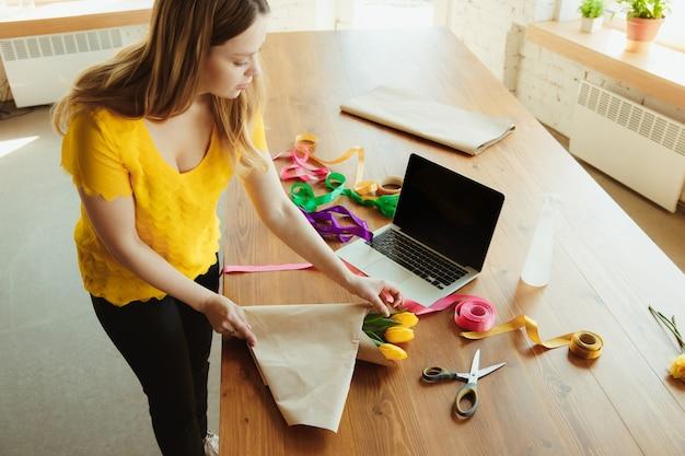 仕事中の花屋:女性はチューリップで花束を作る方法を示しています。若い白人女性は、お祝いのためにプレゼントをするギフトを行うオンラインワークショップを提供します。隔離され、隔離された概念で在宅勤務。