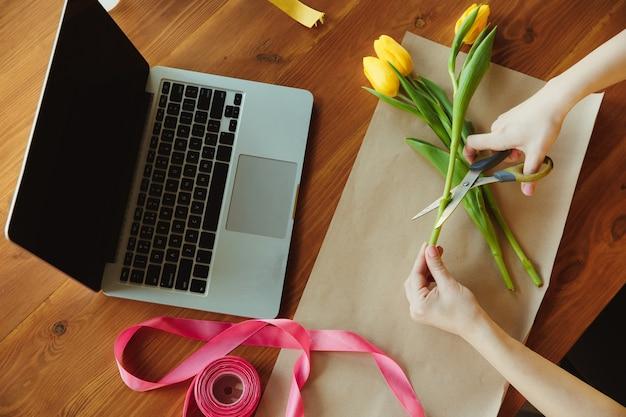 職場の花屋: チューリップで花束を作る方法を示す女性。
