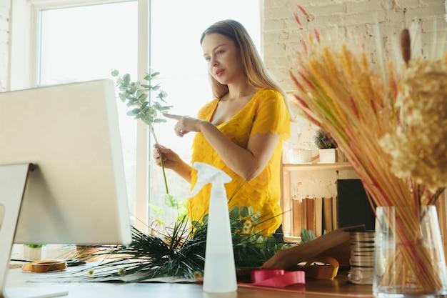Флорист за работой женщина показывает, как сделать букет, работая дома концепция, выбирая растения для композиции