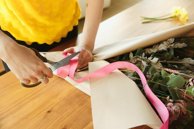 在宅勤務の女性の花屋は、自宅で花束を機能させる方法を示していますコンセプトをクローズアップ