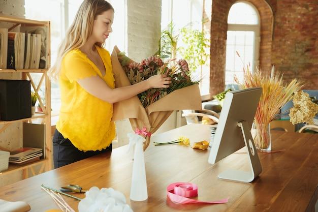 Флорист за работой женщина показывает, как сделать букет, работая дома концепции, демонстрируя результат