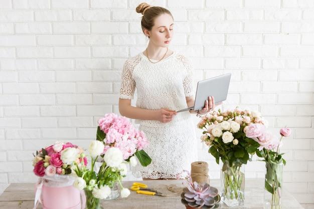 花屋は仕事の前に注文リストを確認します。フラワーショップでノートを持つビジネスウーマン。中小企業経営、女性マネージャー、時間管理、オンライン花販売コンセプト
