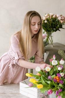 플로리스트는 꽃다발을 위해 꽃을 선택합니다. 데코레이터 워크숍. 꽃집에서 여자, 튤립 구색에 대한 돌보는
