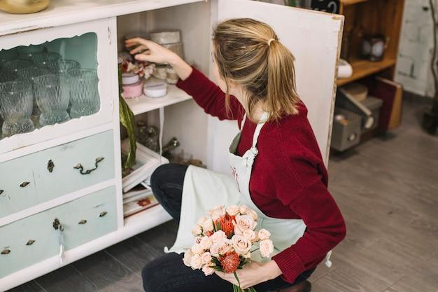 Флорист выбирает украшения для букета
