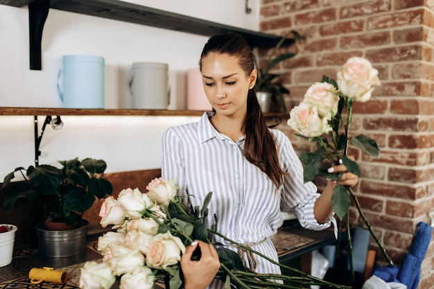 꽃집에서 꽃집에서 아름다운 네덜란드 장미 꽃다발을 수집합니다.