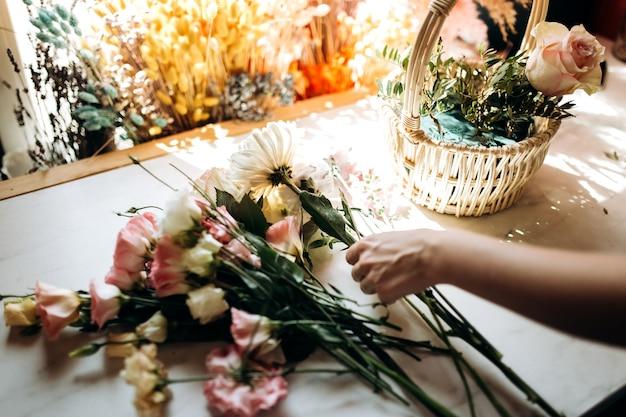 꽃집은 꽃집에서 신선한 카모마일과 eustoma에서 바구니에 꽃다발을 수집합니다.