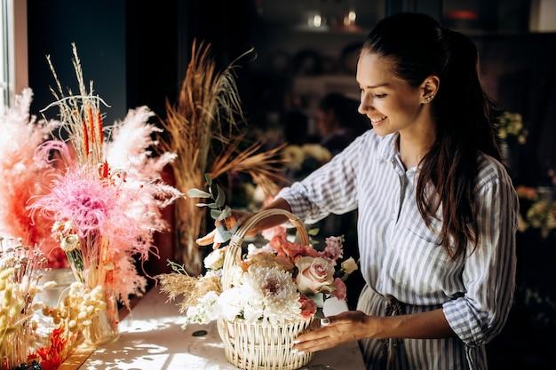 꽃집은 꽃집에서 파스텔 색상의 신선한 꽃으로 바구니에 꽃다발을 수집합니다.