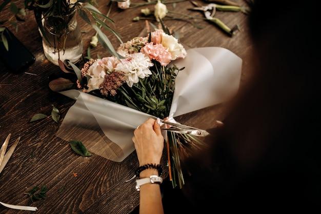 꽃집은 파스텔 색상의 신선한 꽃 꽃다발에 리본을 자릅니다. .