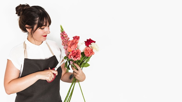 Florist cutting twigs of flowers with scissors on white backdrop
