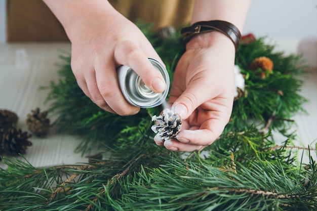 Florist decorator making christmas wreath