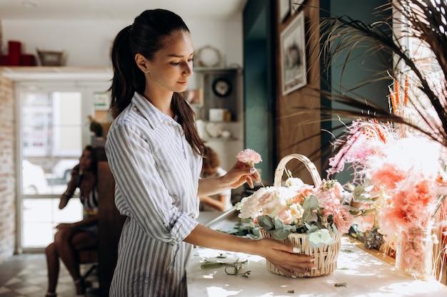 줄무늬 드레스를 입은 꽃집은 꽃집에서 파스텔 색상의 신선한 꽃으로 바구니에 꽃다발을 수집합니다.