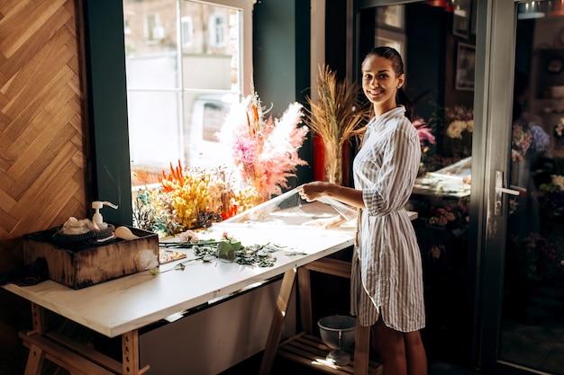 줄무늬 드레스를 입은 꽃집은 화려한 말린 꽃이 있는 테이블 근처에 서서 꽃 가게에서 투명한 포장 봉투를 들고 있습니다.