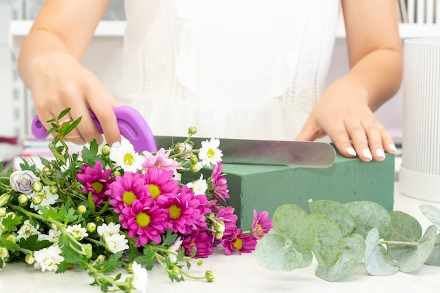 Florist girl working in a flower shopgirl florist cuts oasis with a knife floristry business floristry courses