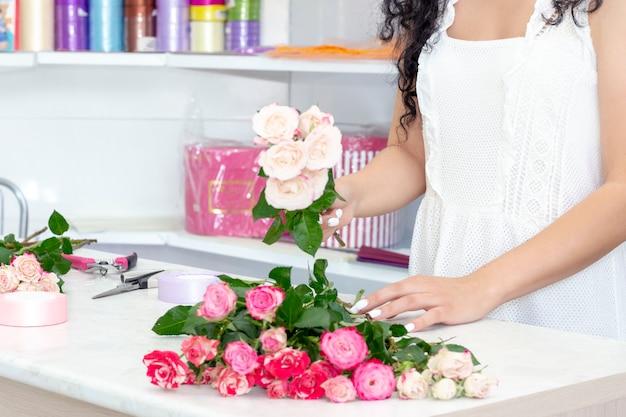 Флорист девушка работает в цветочном магазине. мягкие оттенки свежих весенних цветов учитесь, чтобы мастер флорист делится своими навыками, показывая, как расположить цветы в идеальный красивый букет