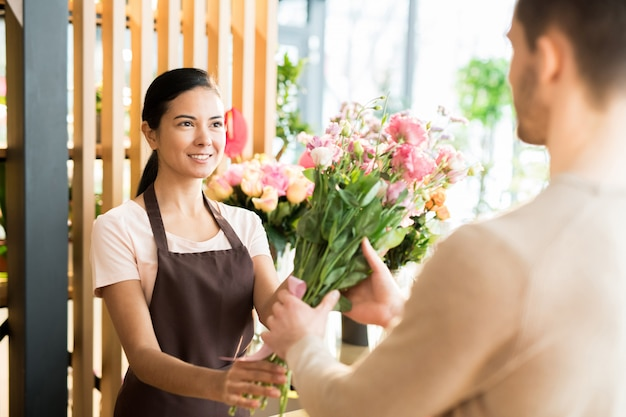 Florist giving bouquet to buyer