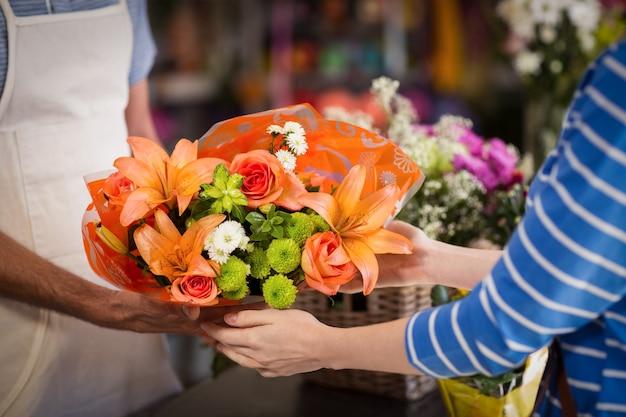 고객에 게 꽃의 꽃다발을주는 꽃집