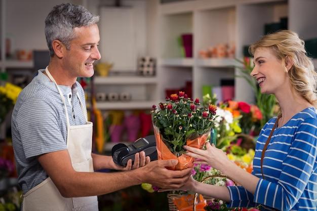 여자에 게 꽃의 꽃다발을주는 꽃집