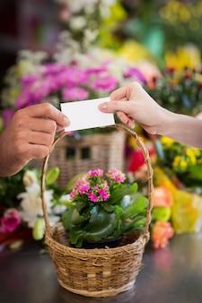 고객에게 방문 카드를주는 꽃집