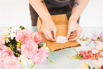 Florist hand sticking label on paper bag with flowers on desk