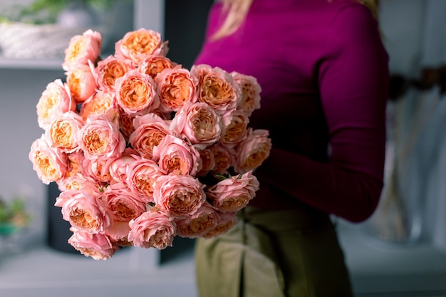 플로리스트는 꽃다발을 들고입니다. 아름다운 봄 꽃. 믹스 꽃과 배열. 꽃집, 소규모 가족 사업의 개념. 작업 플로리스트. 복사 공간