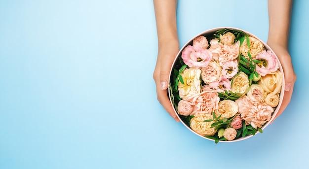 Флорист держит шляпу круглую коробку с цветочным составом на синем фоне с копией пространства. подарочная коробка на 8 марта, день святого валентина, день матери, день рождения. свадьба.