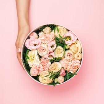 Флорист держит шляпу круглую коробку с цветочным составом на розовом фоне с копией пространства. подарочная коробка на 8 марта, день святого валентина, день матери, день рождения. свадьба.