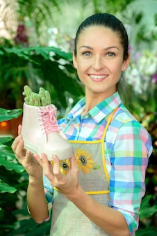 Florist holds shoes and a flower is planted inside.