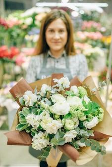 Флорист в фартуке со свежим букетом в цветочном магазине