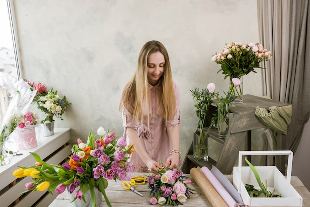 ワークショップの花屋は花束を詰めます。デコレータは彼女の作品で動作します。フローリストリーを組み立てるフラワーショップの女性