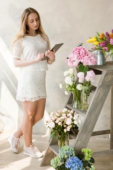 花屋はさまざまな花を検査します。フラワーショップでタブレットを持つビジネス女性。中小企業経営、女性マネージャー、時間管理、オンライン花販売コンセプト